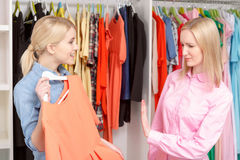 Woman chooses dress in a store Royalty Free Stock Photography