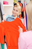 Woman chooses dress in a store Royalty Free Stock Image