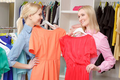 Woman chooses dress in a store Royalty Free Stock Images