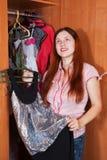 Woman chooses dress in wardrobe Stock Image
