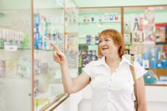 Woman chooses drugs at pharmacy Royalty Free Stock Photography