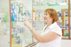 Woman chooses drugs at pharmacy Royalty Free Stock Images