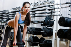 Woman chooses dumbbells Stock Images