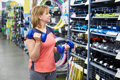 Woman chooses dumbbells for fitness in sports shop Stock Image
