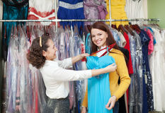 Woman chooses evening dress at clothing shop. Young women chooses evening dress at clothing shop. Friendly shop consultant helps her Royalty Free Stock Photos