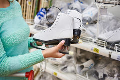 Woman chooses figure skates in sports shop Royalty Free Stock Photos