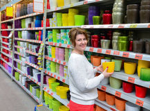 Woman chooses a flower pot in store Royalty Free Stock Images