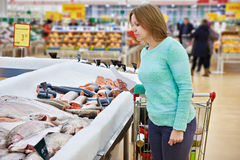 Woman chooses fresh fish in supermarket Stock Photography