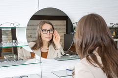 Woman chooses glasses stock photography