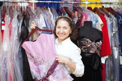 Woman  chooses gown at clothing store Royalty Free Stock Images