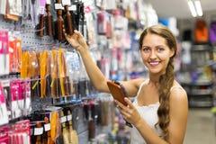 Woman chooses hairbrush Stock Image