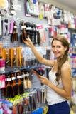 Woman chooses hairbrush. Smiling woman chooses hairbrush in hardware store royalty free stock photos