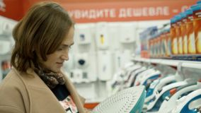 A woman chooses an iron in a home appliance store. The brunette chooses the iron as a gift. stock video footage