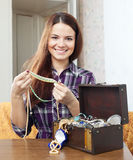 Woman chooses jewelry in treasure chest Royalty Free Stock Photography