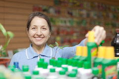 Woman chooses  liquid fertilizer at store Stock Image