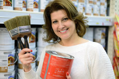Woman chooses paint and brushes in store Stock Images