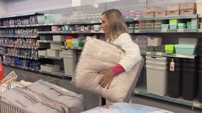 A woman chooses a pillow in the store.  stock video