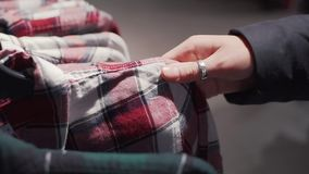 Close up shot of a woman chooses plaid shirt in a fashion boutique.