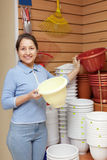 Woman chooses plastic flower pot in  store Royalty Free Stock Photography