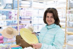 The woman chooses a plate in the store. Woman chooses a plate in the store stock images
