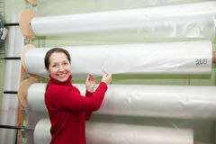 Woman chooses polythene for hothouse. At foil roll in market royalty free stock image