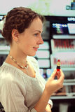 Woman chooses red lipstick in store Royalty Free Stock Photography