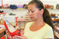 Woman chooses red shoes in a store Stock Image