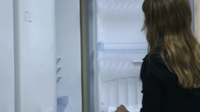 Woman chooses refrigerator. Supermarket stock footage
