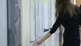 Woman chooses refrigerator. Supermarket stock video footage