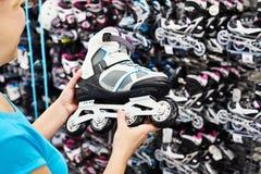 Woman chooses roller skates in sports shop Stock Photos