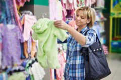 Woman chooses rompers in store Stock Photography