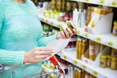 Woman chooses seasoning pesto in grocery store Stock Photo
