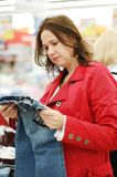 Woman chooses in shop. Clothes royalty free stock images