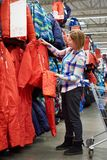 Woman chooses ski jumpsuit in sport store. Woman chooses a ski jumpsuit in a sports store Royalty Free Stock Photo