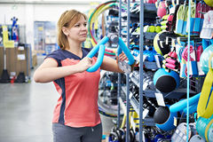 Woman chooses sport equipment. For fitness in the sports shop Stock Photos
