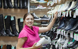 Woman chooses sporty shoes Stock Photography