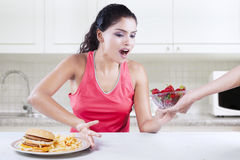 Woman chooses strawberry and refuse burger Royalty Free Stock Images