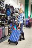 Woman chooses suitcase in shop Royalty Free Stock Photo