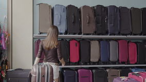 Woman chooses suitcase at shop stock video