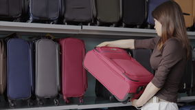 Woman chooses suitcase at shop stock video footage