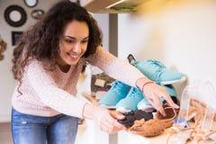 Woman chooses summer shoes at shop Stock Photography
