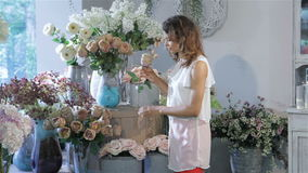 Woman chooses between tea-rose and pink rose at flower shop stock video footage