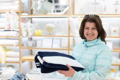 The woman chooses a towel in the store. Woman chooses a towel in the store royalty free stock images
