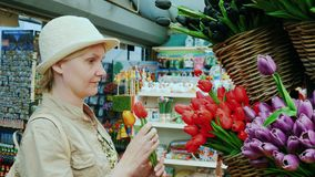 A woman chooses tulips in the famous flower market in Amsterdam. 4K video stock footage