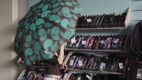 Woman chooses an umbrella in shop stock footage