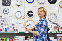 Woman chooses wall clock in store Stock Photography