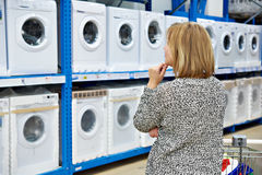Woman chooses washing machine in shop of home appliances. Woman chooses washing machine in the shop of home appliances Stock Photography