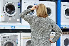 Woman chooses washing machine in shop of home appliances. Woman chooses washing machine in the shop of home appliances Stock Photo