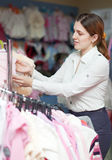 Woman  chooses wear for daughter Stock Photo
