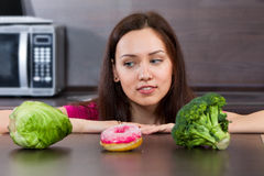 Woman chooses what to eat vegetables or a cake Royalty Free Stock Images